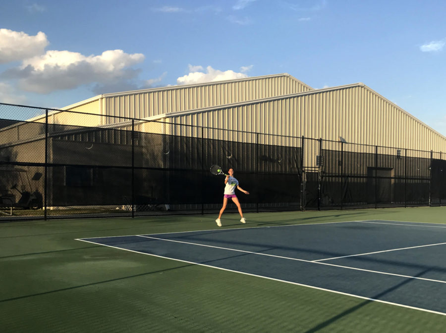 Seventh+grader%2C+Carly+McNatt%2C+practices+skills+at+tennis+practice+after+school.