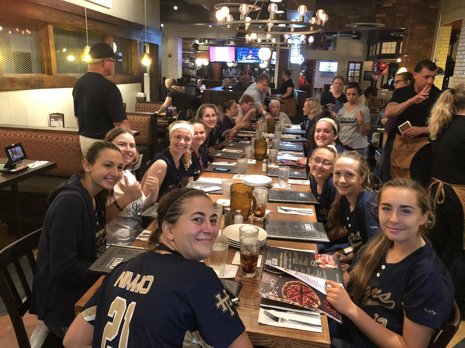 The softball team eats after completing their game.