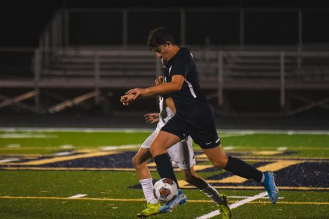 Senior Jackson Mariani dribbles the ball down the field against MCC.